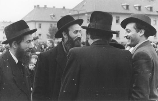 A group of religious Jewish men converse outside at the Bergen Belsen displaced persons camp.jpg